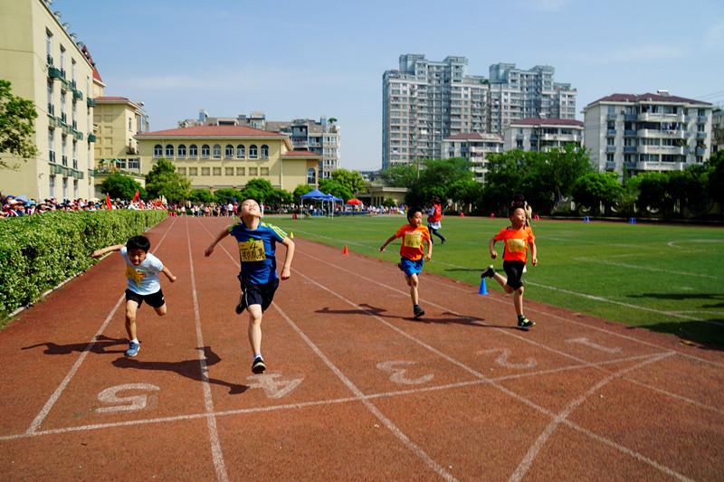 百米跑道上,低年级的小朋友们要紧牙齿,奋力往前冲刺;高年级的运动